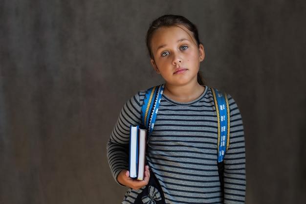 Niña de la escuela linda con libros y mochila en la pared gris