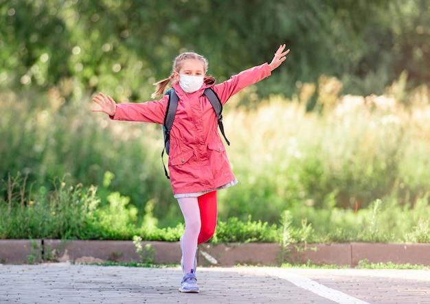 Niña de la escuela en máscara médica corriendo al aire libre después de clases