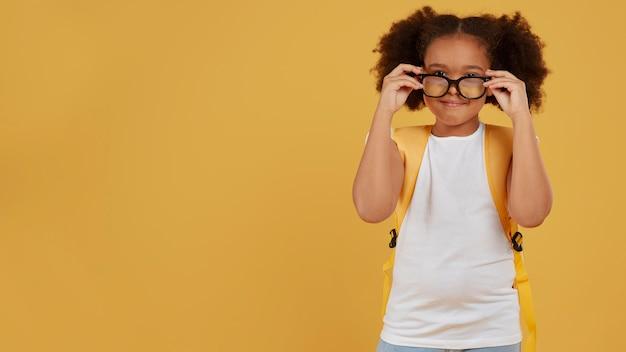Niña de la escuela pequeña arreglando sus gafas para leer espacio de copia