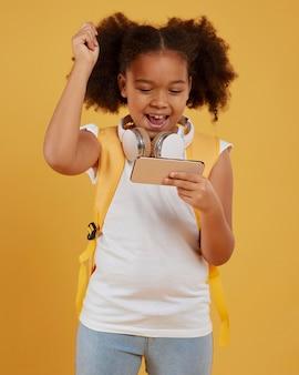 Niña de la escuela pequeña jugando en el teléfono móvil