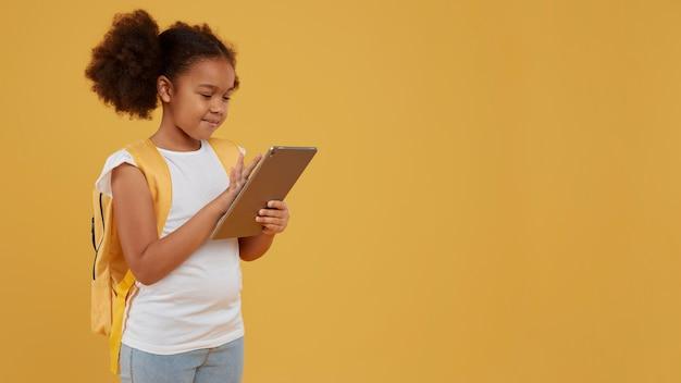 Niña de la escuela pequeña con una tableta digital