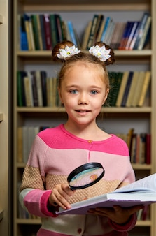 Niña de la escuela de pie con la enciclopedia en la biblioteca, leyendo un libro, obteniendo nueva información para el cerebro