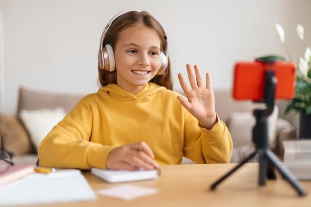 Niña de la escuela positiva con videoconferencia en el teléfono inteligente y lección en línea con el maestro desde casa