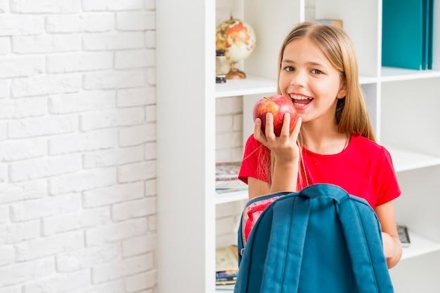 Niña de la escuela primaria con la intención de morder la manzana
