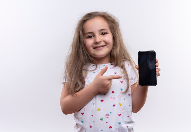 Niña de la escuela sonriente con camiseta blanca apunta al teléfono sobre fondo blanco aislado