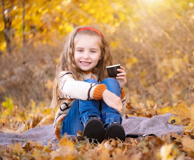 Niña de la escuela sonriente sosteniendo la taza en el bosque de otoño