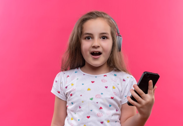 Niña de la escuela sonriente vistiendo camiseta blanca en auriculares sosteniendo teléfono sobre fondo rosa aislado