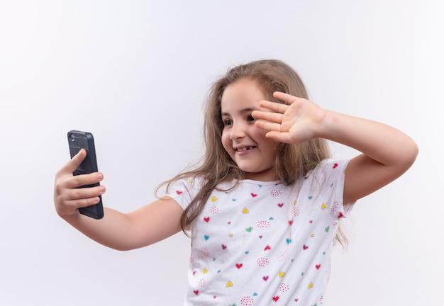 Niña de la escuela sonriente vistiendo camiseta blanca habla por teléfono sobre fondo blanco aislado