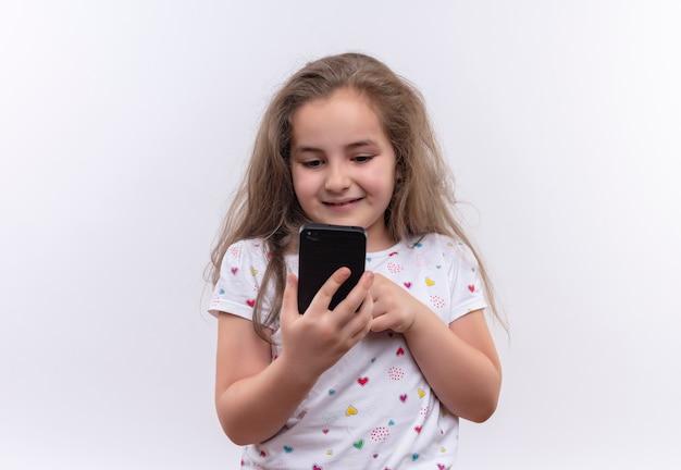 Niña de la escuela sonriente vistiendo camiseta blanca jugando en el teléfono sobre fondo blanco aislado