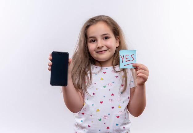 Niña de la escuela sonriente vistiendo camiseta blanca sosteniendo teléfono y marca de papel sobre fondo blanco aislado