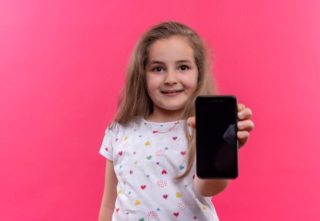 Niña de la escuela sonriente vistiendo camiseta blanca sosteniendo el teléfono sobre fondo rosa aislado