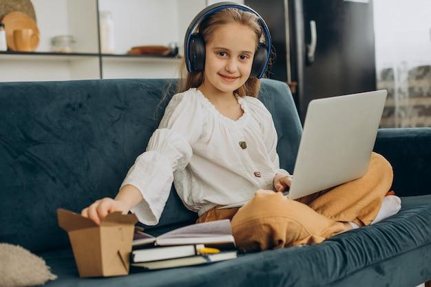 Niña de la escuela viendo la película en la computadora y comiendo palomitas de maíz