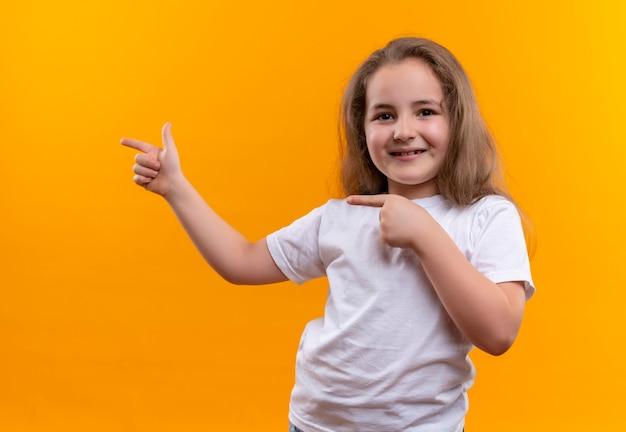 Niña de la escuela vistiendo camiseta blanca apunta al lado de la pared naranja aislada