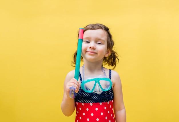 Una niña en un espacio amarillo en un traje de baño con una máscara y snorkel para nadar. la niña sonríe. la niña de las coletas. op¡opia el espacio.