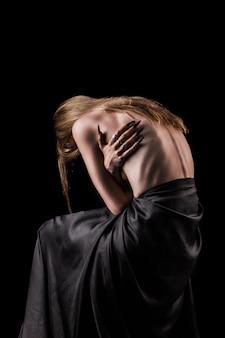 Una niña con la espalda descubierta, delgadez severa y costillas sobresalientes