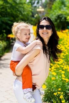 Una niña en la espalda de su madre. la madre sonríe. día de verano.