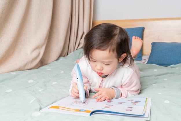 La niña estaba leyendo en la cama