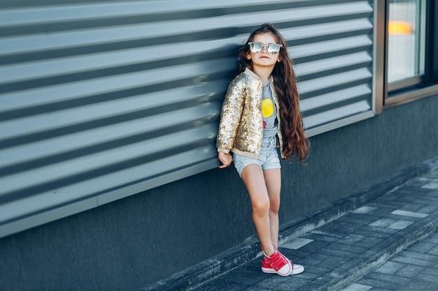 Niña con estilo en gafas de sol de pie cerca de la pared gris