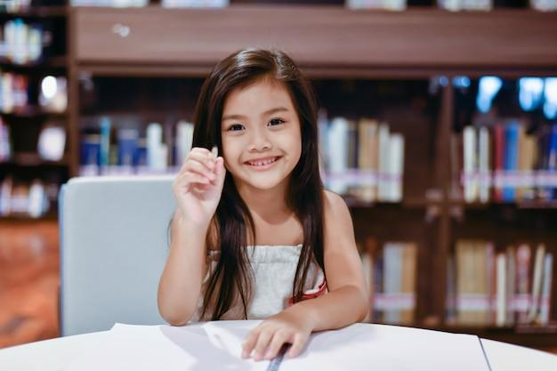 Niña está estudiando en la biblioteca