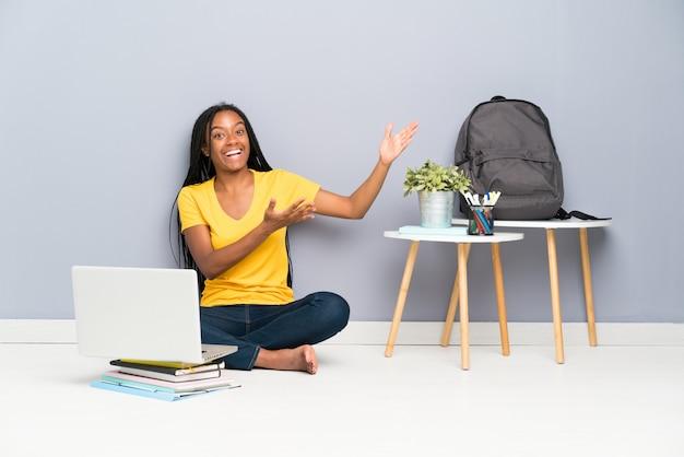 Niña estudiante afroamericana adolescente con cabello largo trenzado sentado en el suelo extendiendo las manos hacia un lado para invitar a venir
