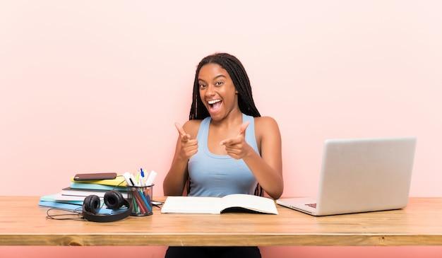Niña estudiante afroamericana adolescente con cabello largo trenzado en su lugar de trabajo que apunta al frente y sonriendo