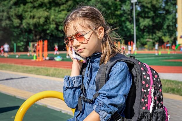 Una niña, una estudiante de escuela primaria con gafas de sol que llama por teléfono, solo habla, se comunica.