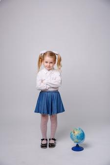 Niña estudiante con globo del mundo sobre fondo blanco.