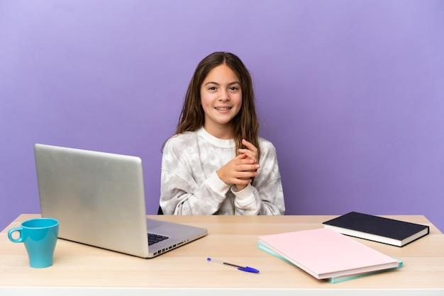 Niña estudiante en un lugar de trabajo con un portátil aislado sobre fondo púrpura aplaudiendo