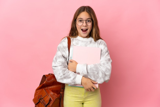 Niña estudiante sobre pared rosa aislada con expresión facial sorpresa