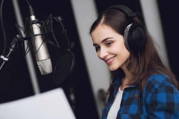 La niña en el estudio de grabación canta una canción.