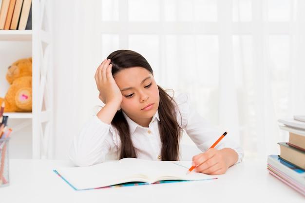 Niña étnica estudiando en casa