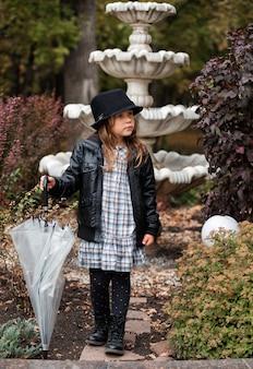 Niña europea en chaqueta de cuero con paraguas en el parque otoño