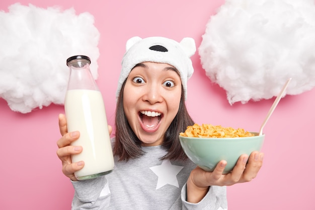 Niña exclama en voz alta que va a tener un delicioso desayuno saludable posa con cereales y leche aislado en rosa