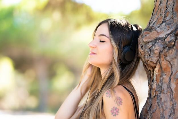 Niña en el exterior en un parque escuchando música