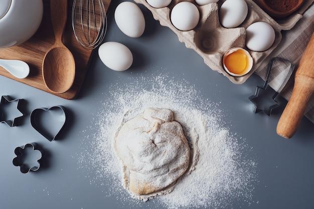 La niña extiende la masa con un rodillo de madera para hacer cupcakes o galletas. composición plana con utensilios e ingredientes de cocina, espacio de copia. concepto de repostería para las vacaciones.