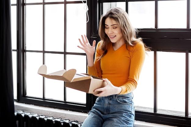 Niña feliz abre una caja de cortón en casa, entrega, correo y concepto de personas