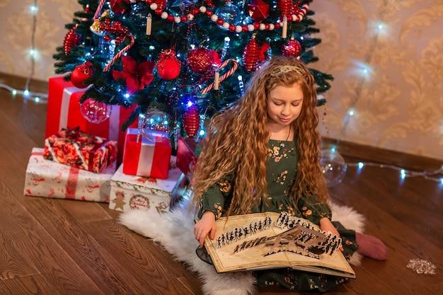 Niña feliz abriendo y leyendo un libro cerca del árbol de navidad