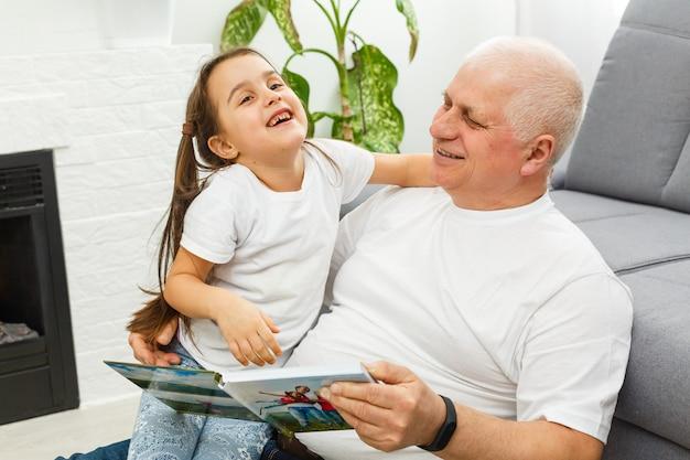 Niña feliz con el abuelo leyendo el libro de cuentos en casa