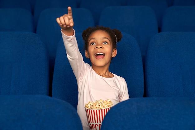 Niña feliz apuntando con el dedo a la pantalla y viendo la película