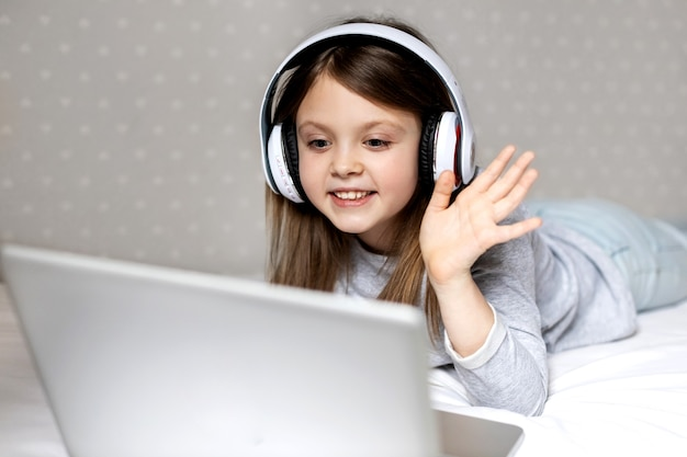 Niña feliz en auriculares inalámbricos se comunica con alegría a través de internet en una computadora portátil