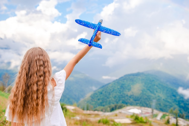 Niña feliz con avión de juguete en manos en las montañas
