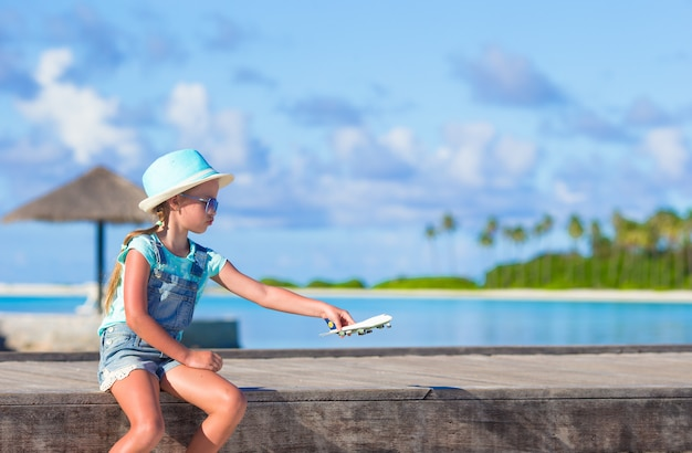 Niña feliz con avión de juguete en manos en la playa de arena blanca