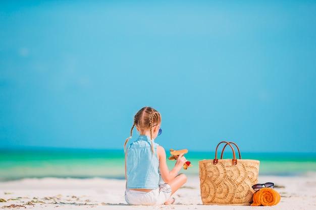 Niña feliz con avión de juguete en las manos en la playa de arena blanca.