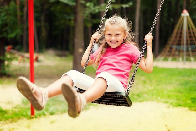 Niña feliz balanceándose en el patio de recreo