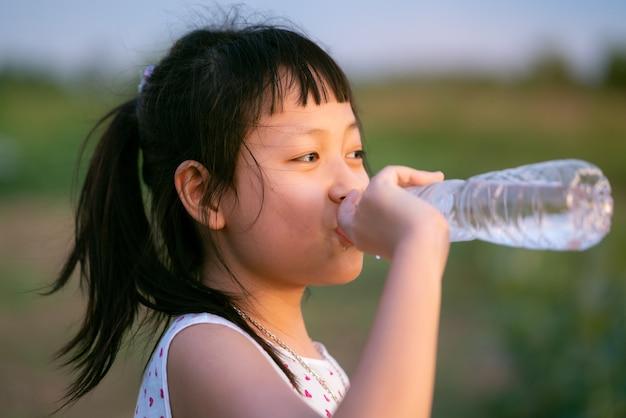 Niña feliz bebiendo agua pura concepto de vida sana