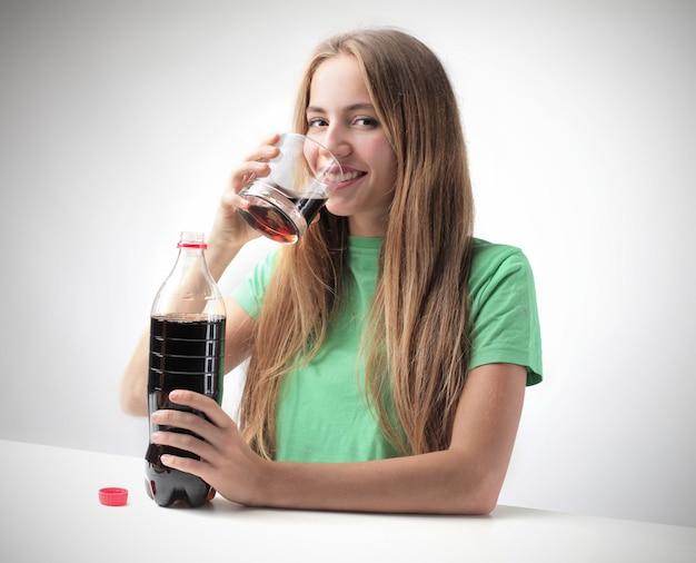 Niña feliz bebiendo coca cola