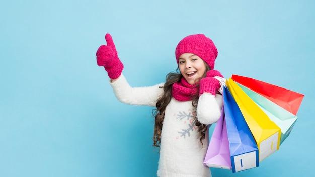Niña feliz con bolsas de compras de ropa de invierno