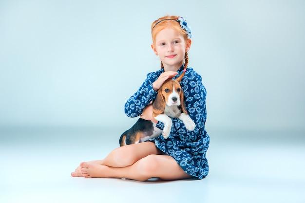 La niña feliz y un cachorro beagle en pared gris