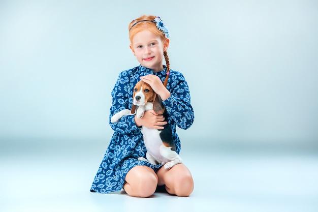 La niña feliz y un cachorro beagle sobre fondo gris