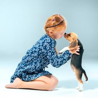 La niña feliz y un cachorro beagle